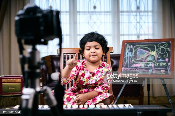 cute girl playing piano while sitting at home - heri mardinal stock pictures, royalty-free photos & images