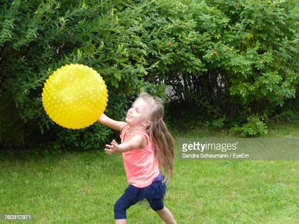 Cute Girl Playing With Ball On Grassy Field At Park
