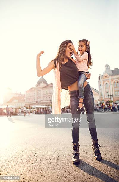 Cute girl playing with her mother by covering her eyes.