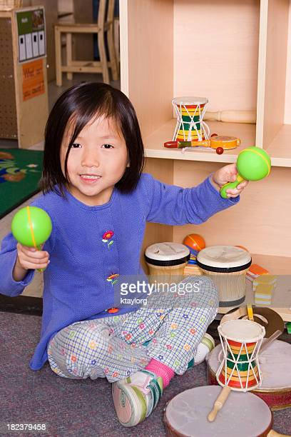 cute girl playing with musical instruments - maraca stock photos and pictures