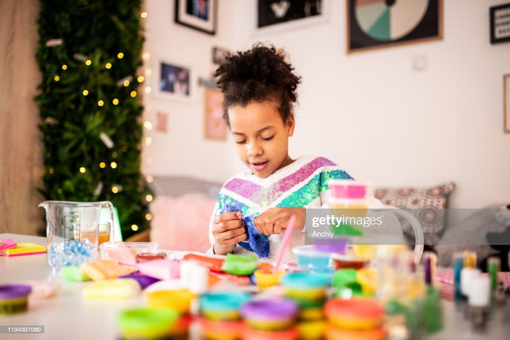 Cute girl playing with slime : Stock Photo