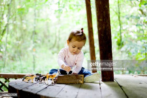 cute girl playing with toy animals - toy animal stock photos and pictures