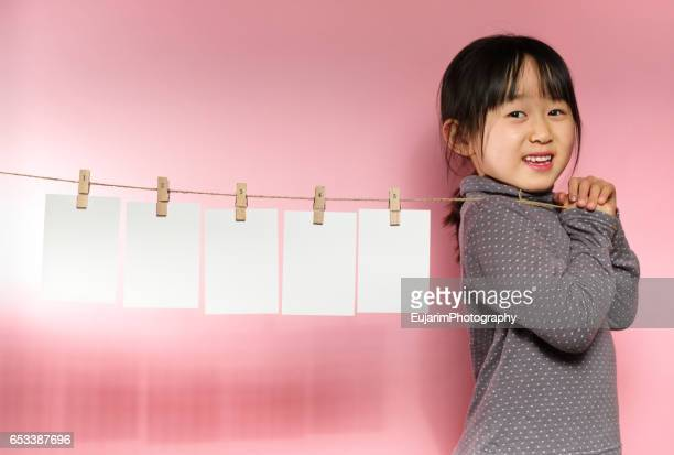 Cute girl pulling a clothesline with five sheets of white paper