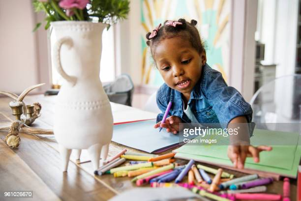 cute girl reaching for colored crayons on table at home - colouring book stock pictures, royalty-free photos & images