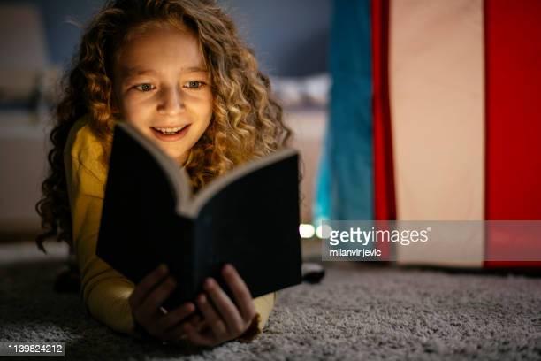 menina bonito que lê um livro em casa - literatura - fotografias e filmes do acervo