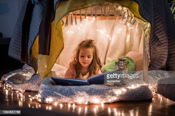 cute girl reading a book in a tent at home. - literature stock pictures, royalty-free photos & images
