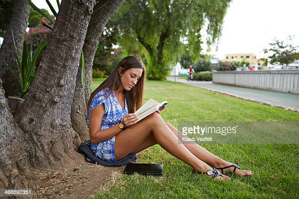 Cute girl reading book under a tree in park