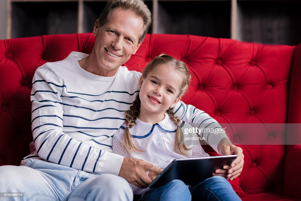 Cute girl resting with her grandfather and holding the tablet : Stock Photo
