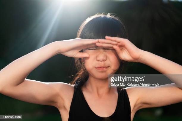 cute girl shielding eyes in yard on sunny day - sleeveless stock pictures, royalty-free photos & images