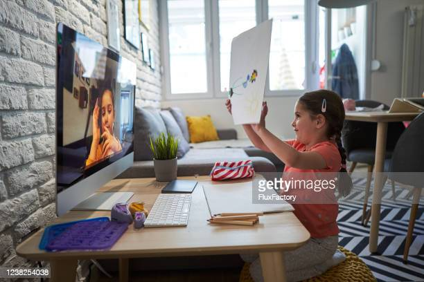 cute girl showing her drawing to her friend during a video call - mindzoom 2 stock pictures, royalty-free photos & images