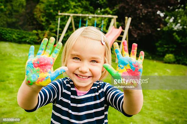 Cute girl showing her hands with finger paint