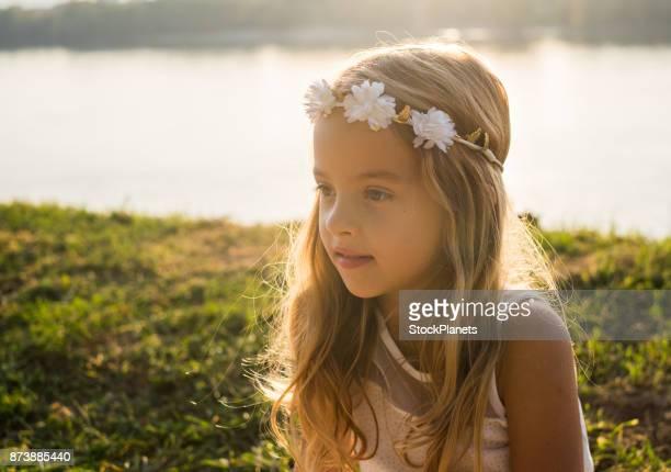 夕日に川岸に座ってかわいい女の子 - 夏休み ストックフォトと画像
