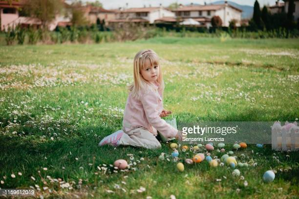 cute girl sitting in field picking up easter eggs, portrait, arezzo, tuscany, italy - italian easter stock pictures, royalty-free photos & images