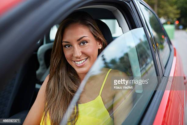 Cute girl sitting in red car & smiling