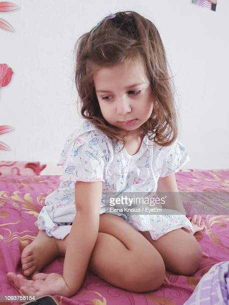 cute girl sitting on bed at home - elena knouzi stock pictures, royalty-free photos & images