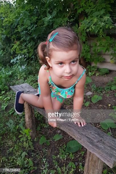 cute girl sitting on bench - elena knouzi stock pictures, royalty-free photos & images