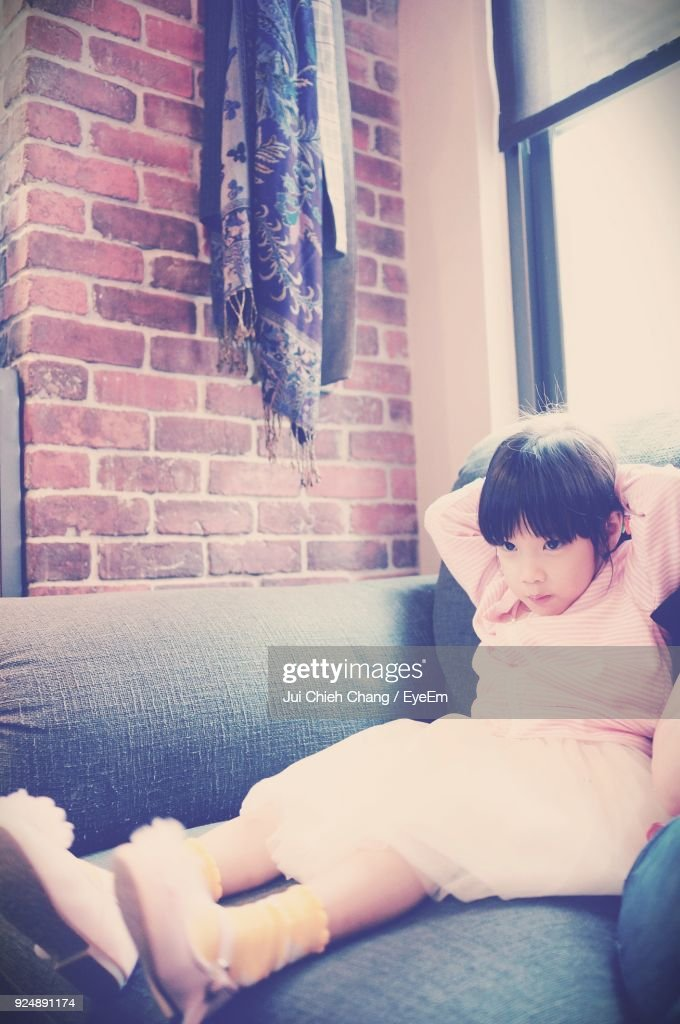 Cute Girl Sitting On Sofa At Home : Stock Photo
