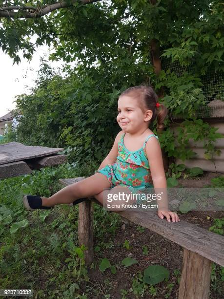 cute girl sitting on wooden bench - elena knouzi stock pictures, royalty-free photos & images