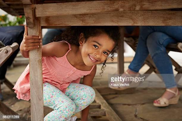 cute girl sitting under table & smiling to camera - unterhalb stock-fotos und bilder