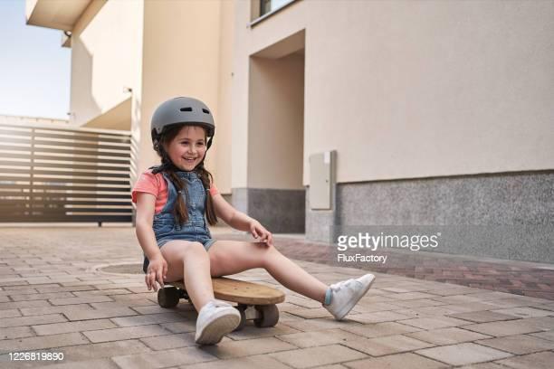 nettes mädchen skateboarding in ihrem hinterhof - ein mädchen allein stock-fotos und bilder