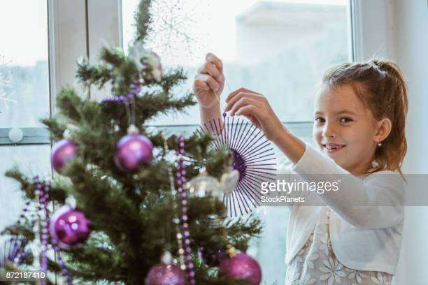 Cute girl smilling and decorating christmas tree