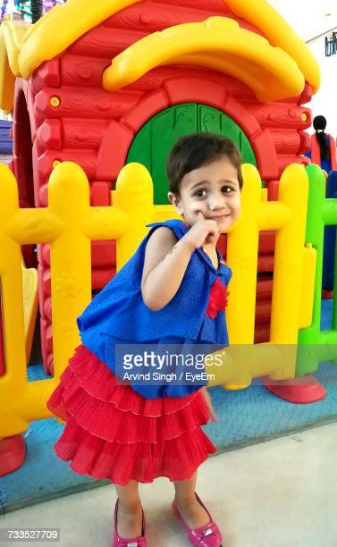 Cute Girl Standing Against Bouncy Castle At Shopping Mall