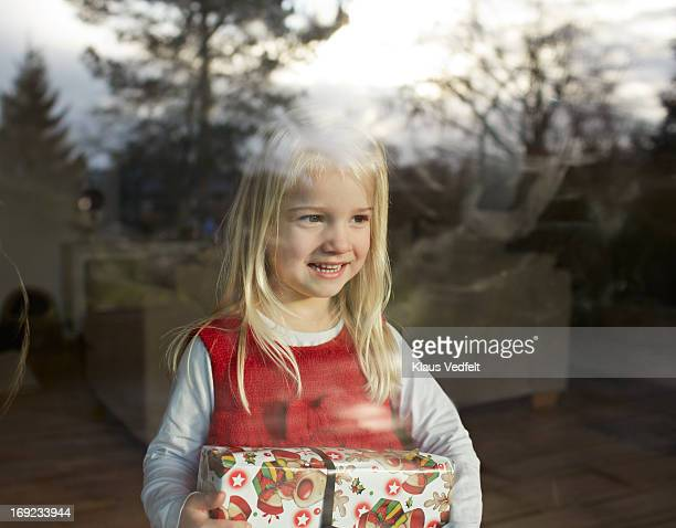 Cute girl standing behind window with present