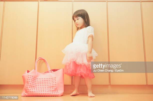 cute girl standing by bag against wall at home - chang jui chieh imagens e fotografias de stock