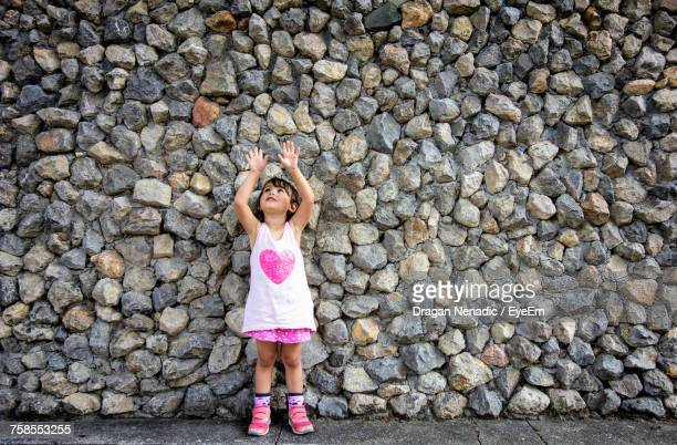 Cute Girl Standing On Street Against Stone Wall