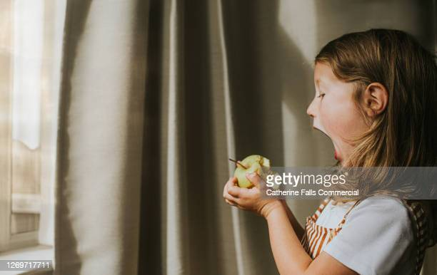 cute girl taking a comically huge bite of a green apple - actress photos stock pictures, royalty-free photos & images