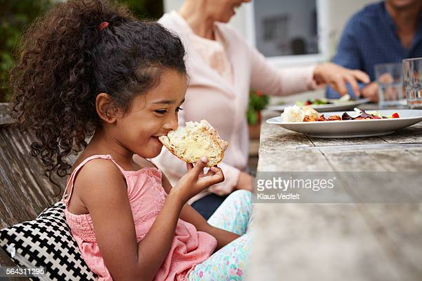 Cute girl taking bite of bread at outside dinner