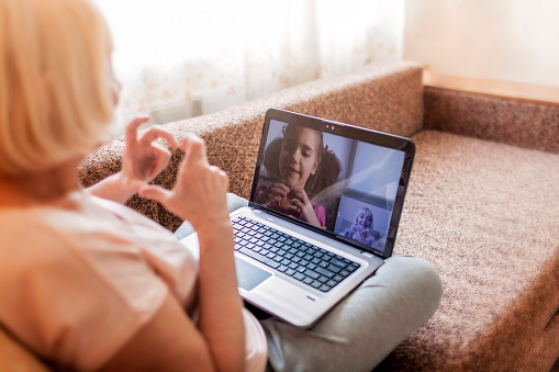 Cute girl talking with her grandmother within video chat on laptop, life in quarantine time 1214116680