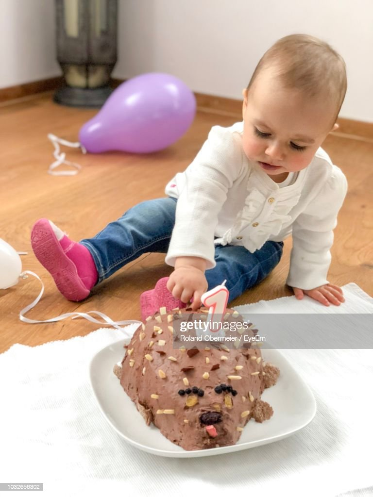 Groovy Cute Girl Touching Birthday Cake In Plate On Floor High Res Stock Funny Birthday Cards Online Overcheapnameinfo