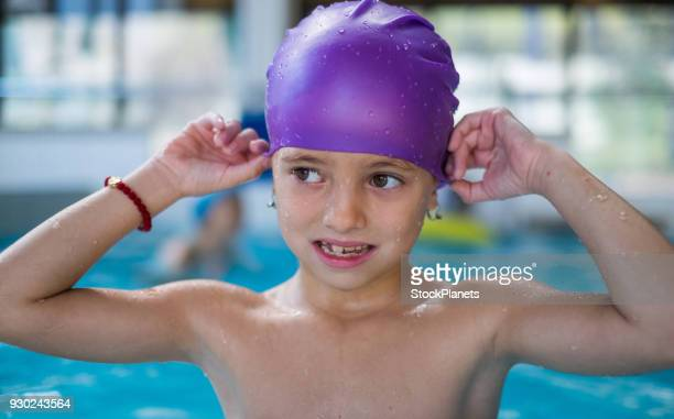 Cute girl trying to put swimming cap in pool