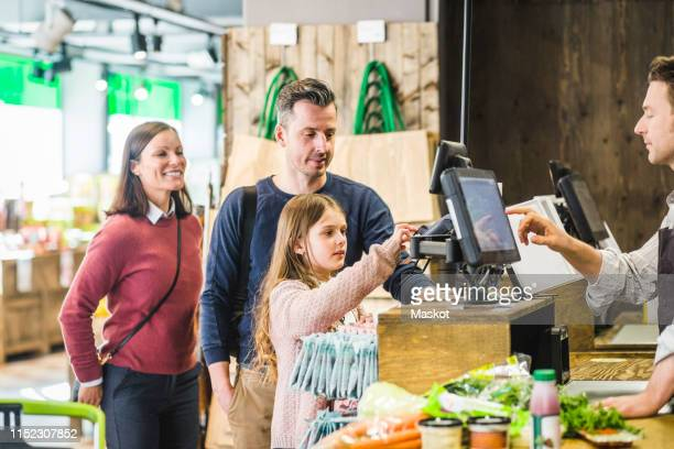 cute girl typing pin code at checkout counter in supermarket by family - 40s pin up girls stockfoto's en -beelden