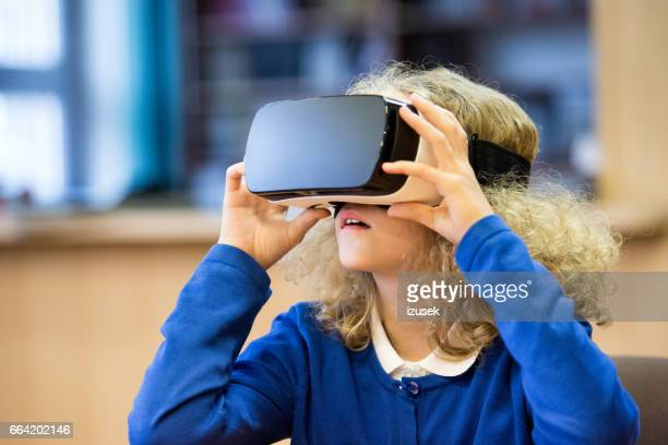 cute girl using virtual reality goggle at school - head mounted display stock photos and pictures