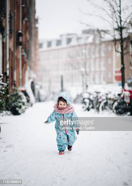 cute girl walking on snowy field in city - warm clothing stock pictures, royalty-free photos & images
