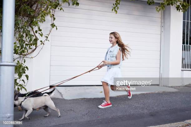 Cute girl walking with dogs on the street