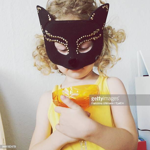 Cute girl wearing mask while holding glass