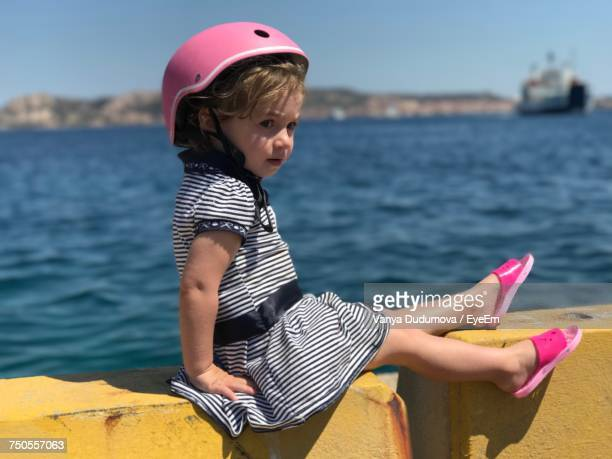 Cute Girl Wearing Pink Helmet Sitting On Retaining Wall Against Sea During Sunny Day