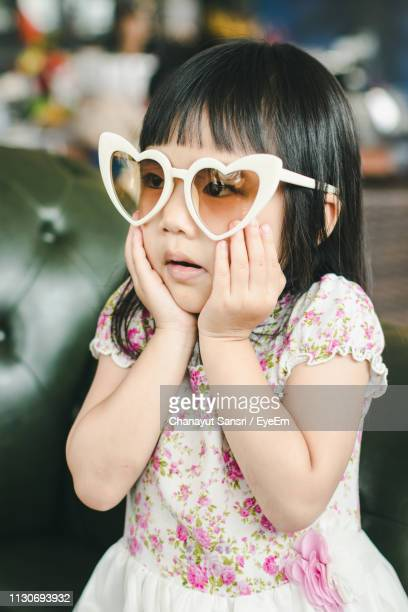 cute girl wearing sunglasses with hands on chin standing indoors - chanayut stock photos and pictures