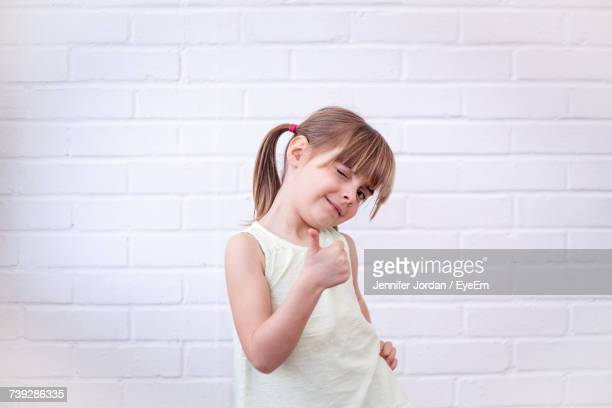 Cute Girl Winking And Gesturing Thumbs Up While Standing Against White Wall