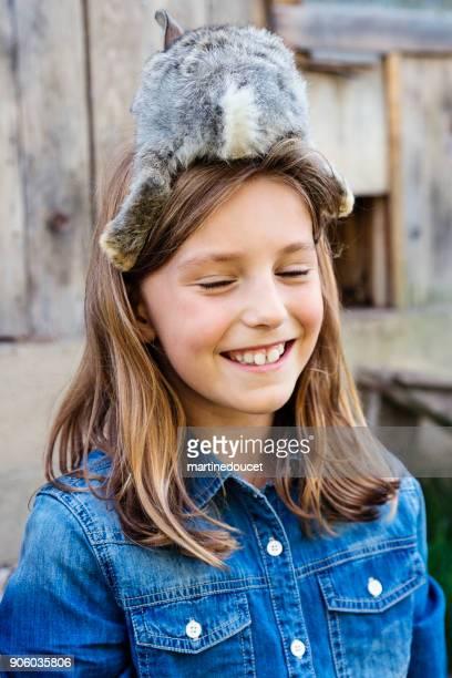 Linda chica con un conejo bebé sobre su cabeza al aire libre en primavera.