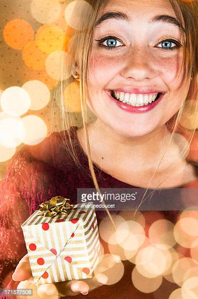 """cute girl with big smile giving a christmas gift. - """"martine doucet"""" or martinedoucet stock pictures, royalty-free photos & images"""