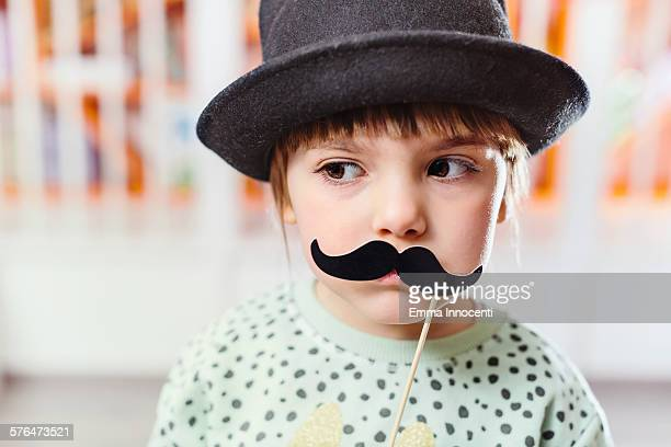 cute girl with black hat and moustaches on stick
