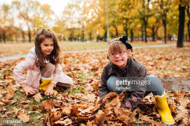 cute girl with down syndrome and her friend playing in fallen leaves - down syndrome stock pictures, royalty-free photos & images