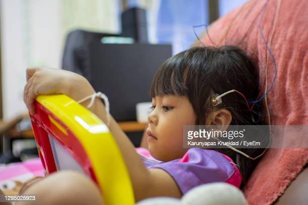cute girl with electrodes on head relaxing on chair - epilepsy stock pictures, royalty-free photos & images