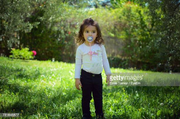 Cute Girl With Pacifier Standing On Grassy Field