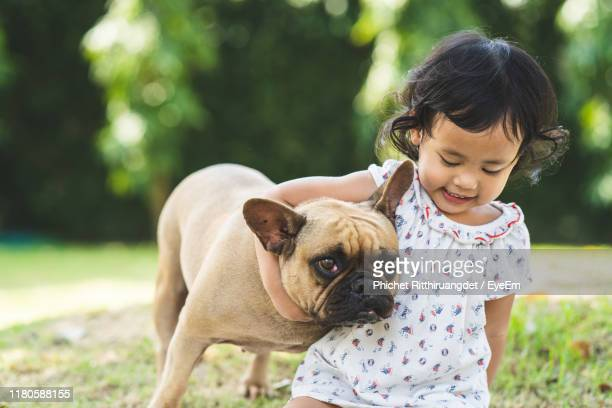 cute girl with pug sitting in park - phichet ritthiruangdet stock photos and pictures