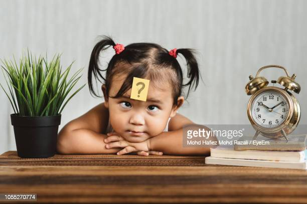Cute Girl With Question Mark On Forehead At Home